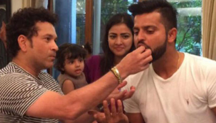 Gracia looks on as father Raina grabs a bite from God of Cricket!